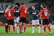 Referee Neil Swarbrick has words with Gary Medel of Cardiff City and Marouane Fellaini of Manchester United after the two of them had a coming together towards the end of the match.<br /> Barclays Premier League match, Cardiff city v Manchester Utd at the Cardiff city stadium in Cardiff, South Wales on Sunday 24th Nov 2013. pic by Phil Rees, Andrew Orchard sports photography,
