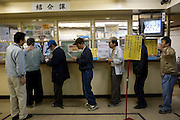 Day laborers queing at Airin Labor Welfare Center for jobs that are offered there..The old name of the area now called Airin, was untill 1966 Kamagasaki and many people still call it like that. .Kamagasaki (????) is an old place name for a part of Nishinari-ku in Osaka, Japan. Airin-chiku (???????) became the region's official name in May, 1966.Sections of four different towns: Nishinari-ku Taishi (??????), Haginochaya (?????), Sanou (???), North Hanazono (????) and Tengachaya (?????) are collectively known as the Kamagasaki region..Kamagasaki as a place name existed until 1922. Kamagasaki is known as Japan's largest slum, and has the largest day laborer concentration in the entire country. 30,000 people are estimated to live in every 2,000 meter radius within this region. An accurate count of occupants has never been produced, even in the national census, due to the large population of day laborers who lack permanent addresses..