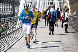 © Licensed to London News Pictures. 20/04/2016. London, UK. People running across the Golden Jubilee Footbridges during the warm weather in central London. The MET Office predict highs of 13 degrees celsius. Photo credit : Tom Nicholson/LNP