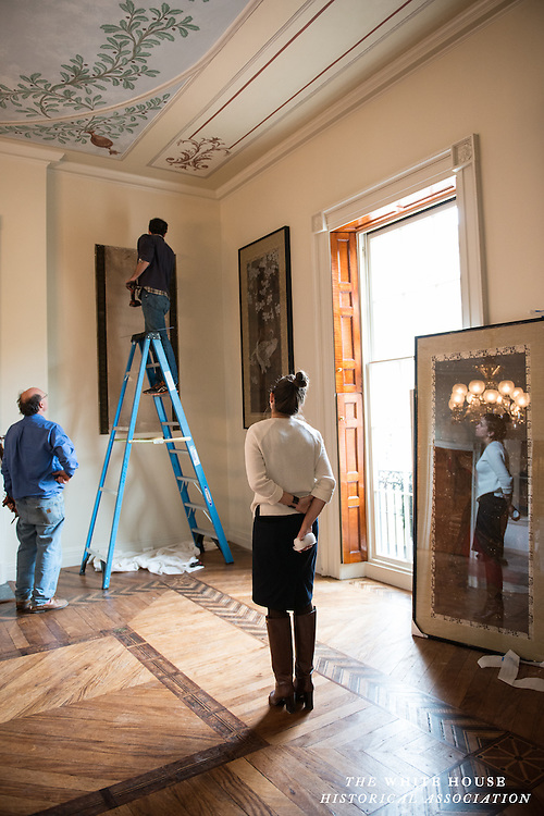 Decatur House Curator Leslie Jones oversees the reinstallation of 100 year old Japanese paintings, which had just been restored, into the second floor Decatur House California Room.