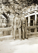 sightseeing friends posing by a traditional bridge Japan 1960s