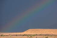 Rainbow on dark rainy sky in the Sahara desert of Morocco.