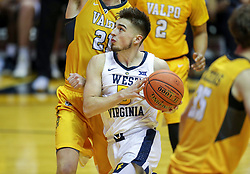 Nov 24, 2018; Morgantown, WV, USA; West Virginia Mountaineers guard Jordan McCabe (5) attempts to dribble past Valparaiso Crusaders defenders during the second half at WVU Coliseum. Mandatory Credit: Ben Queen-USA TODAY Sports