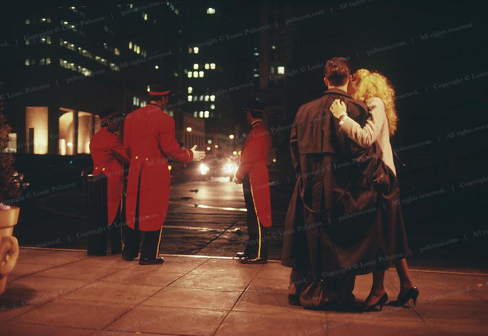 Woman kissing man outside the Grand Hyatt Hotel in New York.