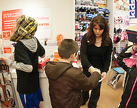 Sales associate Pilar Prete helps children from the Laconia Girls and Boys Club pick out new shoes made possible with a $400.00 grant from Payless Shoes of Gilford Friday afternoon.   (Karen Bobotas/for the Laconia Daily Sun)