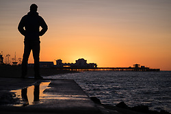 © Licensed to London News Pictures. 12/09/2017. Southsea, UK.  A man watching as the sun rises over Southsea Pier this morning, 12th September 2017. Photo credit: Rob Arnold/LNP