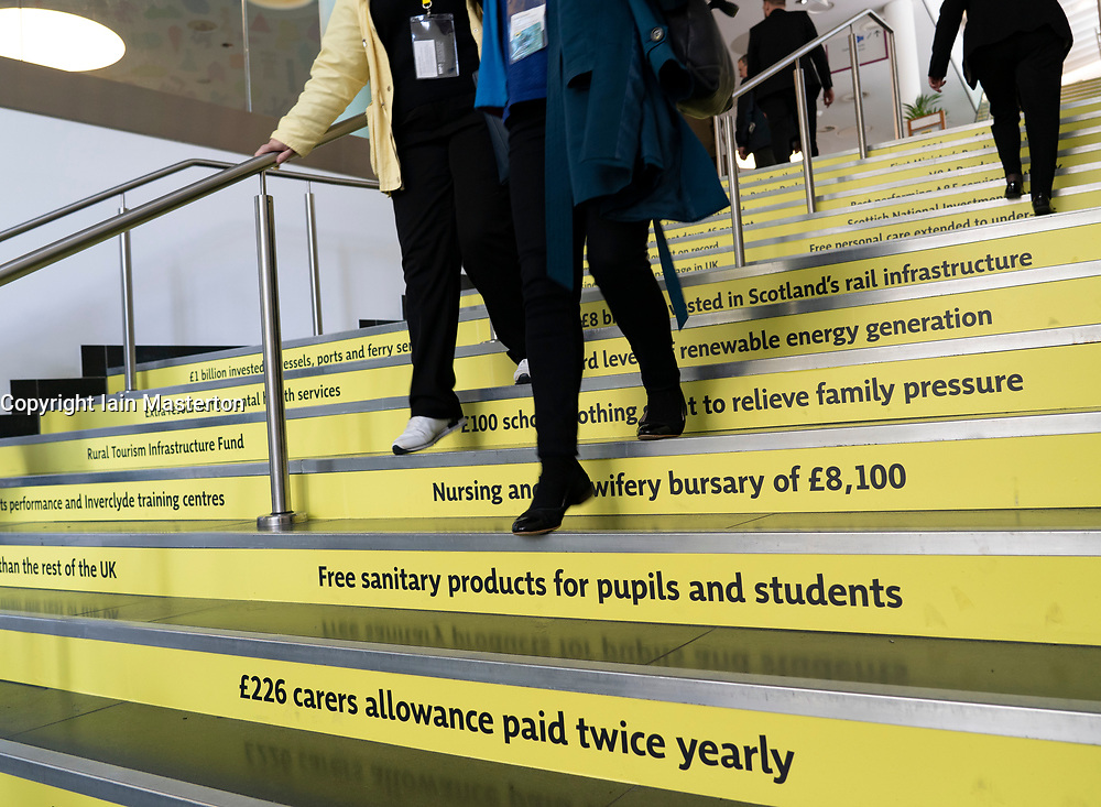 Edinburgh, Scotland, UK. 27 April, 2019. SNP ( Scottish National Party) Spring Conference takes place at the EICC ( Edinburgh International Conference Centre) in Edinburgh. Pictured; Delegates walk down stairs showing  the SNP's. claimed policy highlights