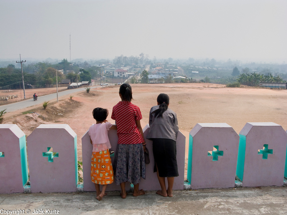 26 FEBRUARY 2008 -- MYAWADDY, MYANMAR: Girls look out over the city of Myawaddy, Myanmar, from the Dae Tain Aung temple. Myawaddy is just across the Moei River from Mae Sot, Thailand and is one of Myanmar's leading land ports for goods going to and coming from Thailand. Most of the businesses in the town are geared towards trade, both legal and illegal, with Thailand. Human rights activists from Myanmar maintain that the Burmese government controls the drug smuggling trade between the two countries and that most illegal drugs made in Myanmar are shipped into Thailand from Myawaddy.   Photo by Jack Kurtz