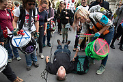 Extinction Rebellion climate change activist and priest lies down in Whitehall to await being arrested by police as sites around Westminster are blocked on 8th October 2019 in London, England, United Kingdom. Extinction Rebellion is a climate group started in 2018 and has gained a huge following of people committed to peaceful protests. These protests are highlighting that the government is not doing enough to avoid catastrophic climate change and to demand the government take radical action to save the planet.