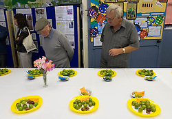 © Licensed to London News Pictures.04/08/15<br /> Egton, UK. <br /> <br /> <br /> Visitors inspect the entries during the annual Egton Gooseberry Show. <br /> There are only two Gooseberry societies left in the country. One in Cheshire and one at Egton in North Yorkshire. The annual show in Egton uses traditional Avoridupois scales to measure the weight of the berries and members of the society are fanatical about trying to grow the best berries each year. <br /> <br /> Photo credit : Ian Forsyth/LNP