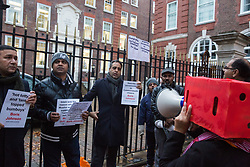 London, UK. 6 December, 2019. A woman holding a red-painted box over her head protests outside the headquarters of the Conservative party against Prime Minister Boris Johnson's likening of Muslim women wearing burqas to letterboxes in an article which he wrote for the Daily Telegraph in August 2018. Other activists held signs highlighting other offensive descriptions used by Mr Johnson and questioned his suitability as Prime Minister.