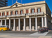 The change of the honour guard on the Plaza Independencia Independence Square. The honour guard guards the mausoleum of General Artigas. Men in old style uniforms marching across a pedestrian crossing supervised by an officer. In front of one of the government buildings Palacio Estavez Palace with a colonnade and a yellow local bus on the street. parade Montevideo, Uruguay, South America