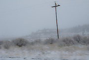 a power pole stands out against the white sky in unseasonable snowy weather along US 550 near the Continental Divide in NW New Mexico, USA  panorama