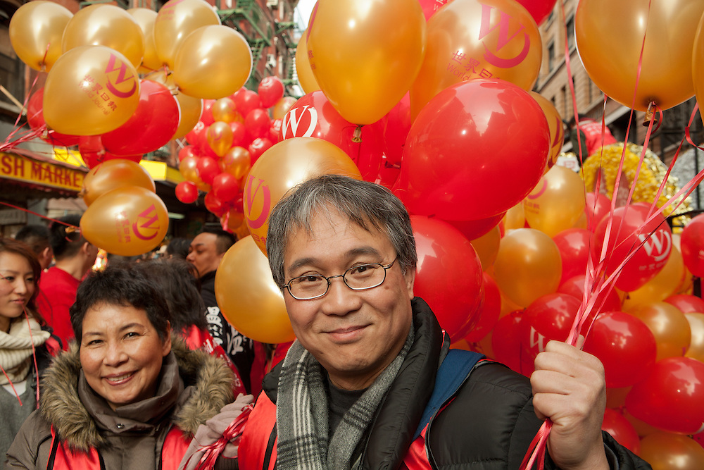 Parade participants holding balloons prior to the start of the parade.