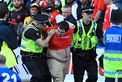 An Arsenal fan is escorted from the ground after the Premier League match at the John Smith's Stadium, Huddersfield.