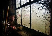 A local dairy farmer peers out of a fogged window at the uninviting weather outside, in Liberty, New York on October 9, 2005.