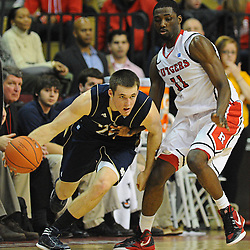 Notre Dame Fighting Irish guard/forward Pat Connaughton (24) dribbles against Rutgers Scarlet Knights guard/forward Dane Miller's (11) defense during Big East NCAA action during Rutgers' 65-58 victory over Notre Dame at the Louis Brown Athletic Center in Piscataway, N.J.