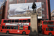 A giant billboard ad for the use of iPhones seen on the side of a central London building, juxtaposed with bus advertising and a WW1 memorial soldier of the Royal Fusiliers.