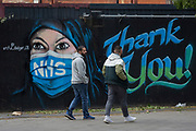 The day after UK Prime Minister Boris Johnson addressed the nation with his roadmap for the coming weeks and months during the Coronavirus pandemic lockdown, two Londoners walk past a mural created by the anonymous street artist known as 'Artful Dodger' (after Charles Dickens's pickpocket character in Oliver Twist), of a Muslim NHS (National Heath Service) nurse wearing a surgical face mask, at Elephant & Castle in south London, on 11th May 2020, in London, England.