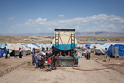© Licensed to London News Pictures. 12/05/2013. Dohuk, Iraq. Young Syrian refugees collect water from a tanker at a refugee camp in Iraqi-Kurdistan, set up for Syrians escaping the ongoing civil war. The camp, close to the city of Dohuk, now houses in the region of 45,000 refugees, with around 400 new arrivals every day. Photo credit: Matt Cetti-Roberts/LNP