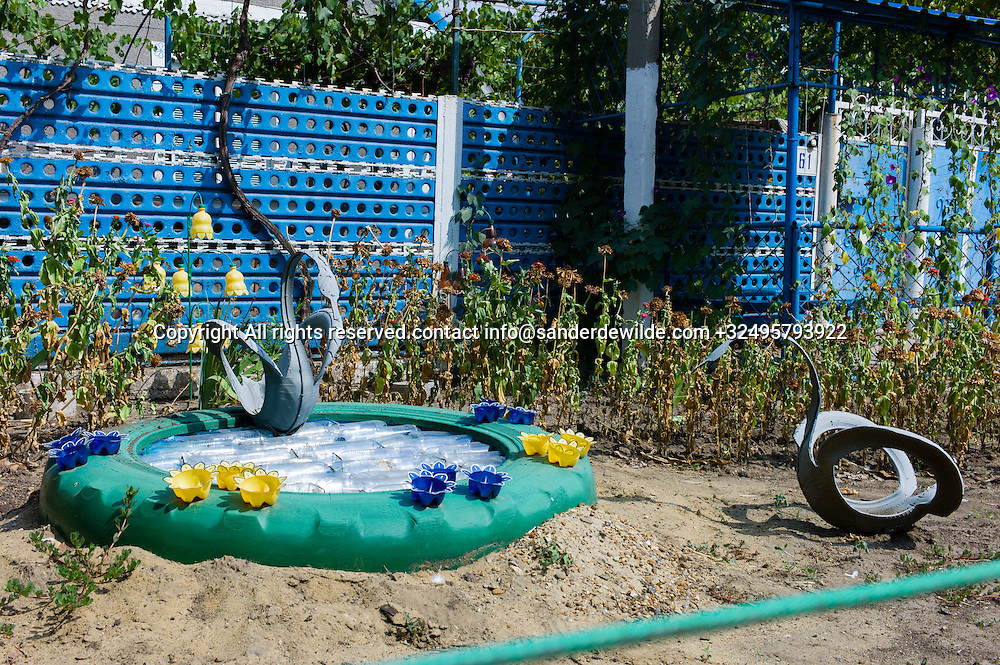 20150828  Moldova, Transnistria,Pridnestrovian Moldavian Republic (PMR) Frunze.creaitivity using old tractor tires and empty bottles you can find every now and then, like this romantic scene with swans and a pond, painted in bright colors