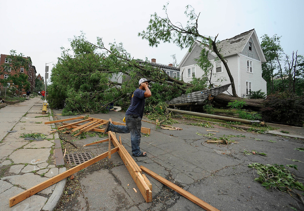 A man talks on his phone near storm damage after a reported tornado struck downtown Springfield, Mass.  A tornado struck downtown Springfield, one of Massachusetts' largest cities, scattering debris, toppling trees, and frightening workers and residents. (AP Photo/Jessica Hill)