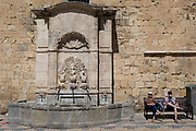 Resting travellers and fountains at the foot of the tall walls of the Archbishop's Palace, on 23rd May, 2017, in Narbonne, Languedoc-Rousillon, south of France.