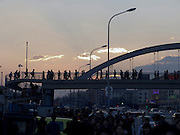 commuters crossing a bridge set against an colorful evening sky Beijing China