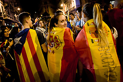 October 3, 2017 - Barcelona, Catalonia, Spain - Young women wrapped with Spanish flags and a man wrapped with a estelada or independentist flag  take part together in a protest against Spanish police brutality in Barcelona. General strike day with massive demonstrations over Catalan territory to protest against brutality by police during a referendum on the region's secession from Spain that left near nine hundred of people injured. (Credit Image: © Jordi Boixareu via ZUMA Wire)