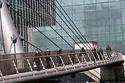 People walk across the South Quay footbridge across the South Dock in Docklands, River Thames, London, England, UK.  The bridge was built in 1997 and serves as a main access point for city worker commuters to walk into Canary Wharf financial district.