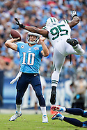 NASHVILLE, TN - SEPTEMBER 29:  Jake Locker #10 of the Tennessee Titans looks to throw a pass while under pressure from Antwan Barnes #95 of the New York Jets at LP Field on September 29, 2013 in Nashville, Tennessee.  The Titans defeated the Jets 38-13.  (Photo by Wesley Hitt/Getty Images) *** Local Caption *** Jake Locker; Antwan Barnes Sports photography by Wesley Hitt photography with images from the NFL, NCAA and Arkansas Razorbacks.  Hitt photography in based in Fayetteville, Arkansas where he shoots Commercial Photography, Editorial Photography, Advertising Photography, Stock Photography and People Photography
