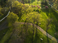 The setting sun shines on Ritter Park in Huntington, West Virginia giving form to trees surrounding the walking paths with early spring greens and blossoms.