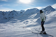 Woman looking over ski slopes while skiing at the Peyragudes ski resort, Midi-Pyrenees, France.