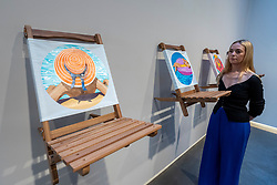 """© Licensed to London News Pictures. 27/05/2021. LONDON, UK. A staff member views deckchair works at the opening of """"You Gave Me Paradise"""", a solo exhibition by British painter Will Martyr at Unit London in Mayfair.  The paintings transport viewers to a space of rest and relaxation in a time when travel restrictions are still in place.  They also reinforce the exhibition's overarching theme of warmth and companionship and are reminiscent, for the artist, of his fondest memories with his wife.   Photo credit: Stephen Chung/LNP"""