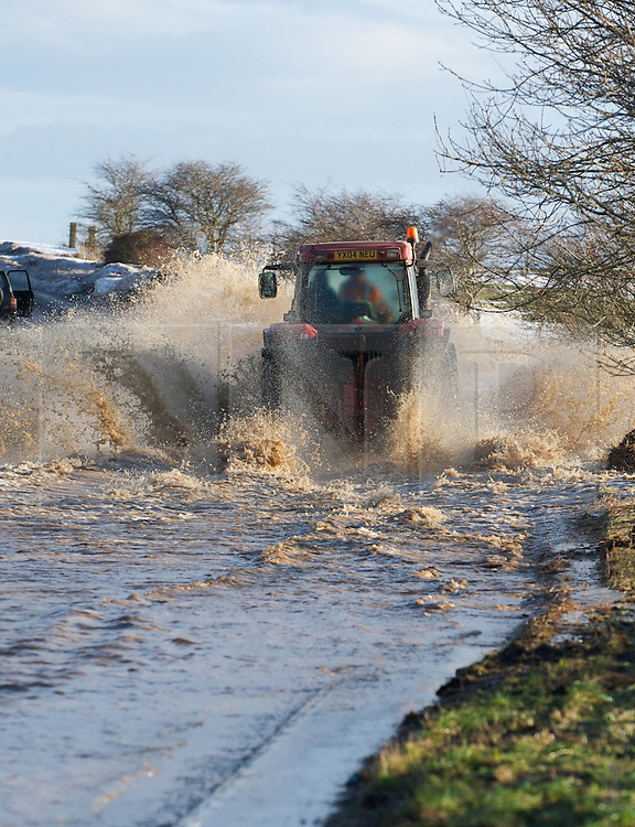 © Licensed to London News Pictures. 27/01/2013..Cleveland, England, UK..Following the recent snowfall a fast thaw through the night brought heavy flooding to some parts of Cleveland and North Yorkshire with many roads closed...A tractor drives easily through deep flood water on a road near to Boulby in East Cleveland...Photo credit : Ian Forsyth/LNP