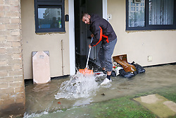 © Licensed to London News Pictures. 08/10/2019. London, UK.  A man sweeps water out of his ground floor flat in Theobalds Court following a burst water main on Brownswood Road in Finsbury Park, north London. Photo credit: Dinendra Haria/LNP