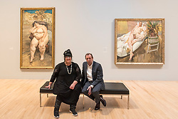 "© Licensed to London News Pictures. 26/02/2018. LONDON, UK. Sue Tilley and David Dawson sit with paintings of themselves by Lucian Freud (L to R) ""Sleeping by the Lion Carpet"", 1996, and ""David and Eli"", 2003-4. ""Preview of ""All Too Human"", an exhibition at Tate Britain which explores how artists in Britain have stretched the possibilities of paint in order to capture life around them.  The exhibition runs 28 February to 27 August 2018 and includes rarely seen works by Lucian Freud and Francis Bacon.  Photo credit: Stephen Chung/LNP"