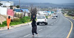 South Africa -Cape Town - 17 August 2020 - A lady carrying wood crosses Baden Powell to Enkanini informal settlement Cape Town,this was preparation for fire as the city is experiencing a cold and wet weather because of a cold front this afternoon .Picture:Phando Jikelo/African News Agency(ANA)