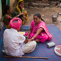 A VHW takes the blood pressure of an elderly man in her village.