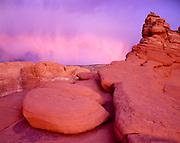 Light of the setting sun illuminating virga falling over the slickrock of Arches National Park, Utah.