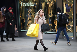 © Licensed to London News Pictures. 19/12/2015. London, UK. A shopper carries her purchases in Oxford Street on the last Saturday before Christmas. Photo credit: Peter Macdiarmid/LNP