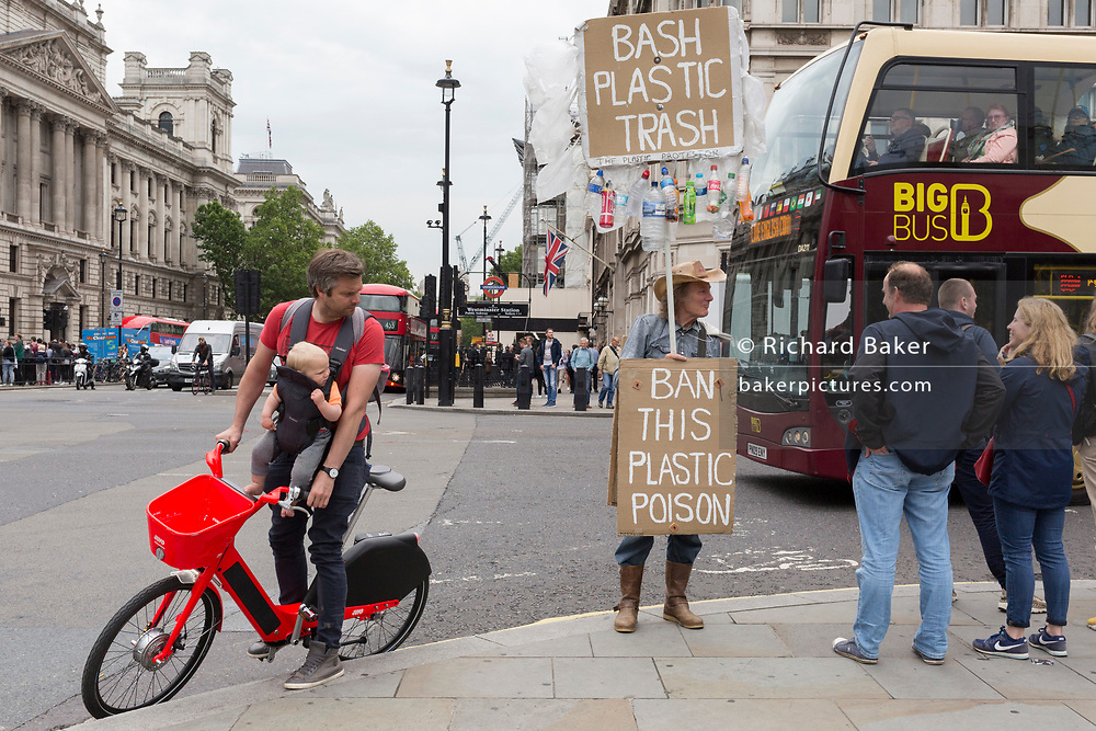 A father cycles looks at a plastics protestor while on a rental bike and carries his child on a chest harness in Parliament Square, Westminster, on 18th June 2019, in London, England.