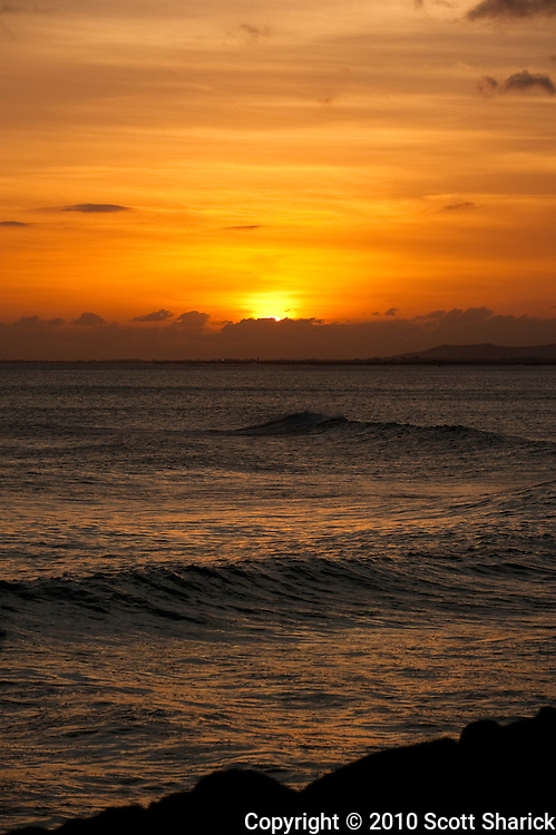 The rocky shore of Oahu with ocean waves and the setting sun.