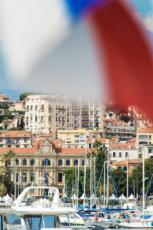 Yachts at Cannes harbor with bleary French flag on foreground and Mairie de Cannes and city on background, Town Hall, Cannes, France