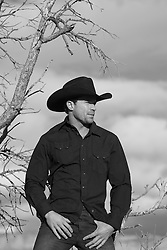 cowboy standing near a pinon tree in New Mexico