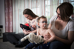 Portrait of Parents with newborn baby boy and little son sitting on the sofa, Munich, Bavaria, Germany