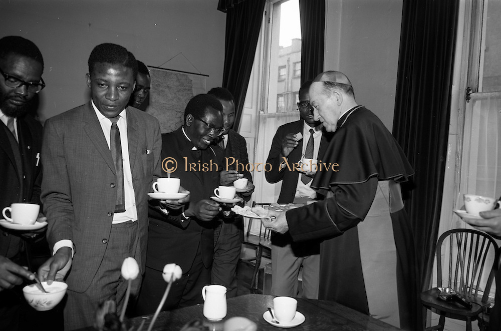 "06/05/1965<br /> 05/06/1965<br /> 06 May 1965<br /> African Students on a visit to Dublin. A group of African students of Catholic Sociology from Claver House, London, on an educational holiday to Ireland. The group stayed with Irish families under the auspices of ""Le Cheile"" a group that promoted friendship and exchange of culture between Irish and overseas people. the students were entertained by His Grace, Most Rev. Dr. McQuaid, Archbishop of Dublin to a visit to the Dublin Institute of Catholic Sociology. Photo Shows the Archbishop entertaining the visitors  to tea and offering Fr. Stefan Haule (Tanzania) a biscuit."