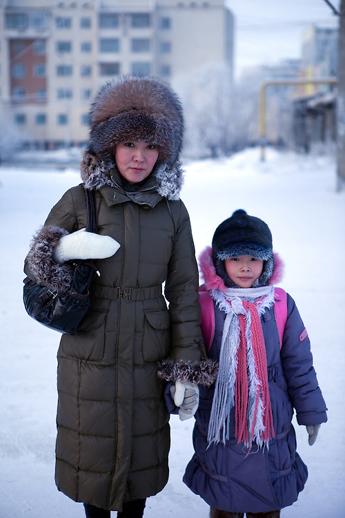 Portrait of a woman and her child in the streets of Yakutsk. Yakutsk is a city in the Russian Far East, located about 4 degrees (450 kilometres) south of the Arctic Circle. It is the capital of the Sakha (Yakutia) Republic in Russia with a major port on the Lena River. The city has a population of 264.000 (2009). Yakutsk is one of the coldest cities on Earth. The average monthly winter temperature in January is around -43,2 C. Yakutsk, Jakutsk, Yakutia, Russian Federation, Russia, RUS, 15.01.2010.