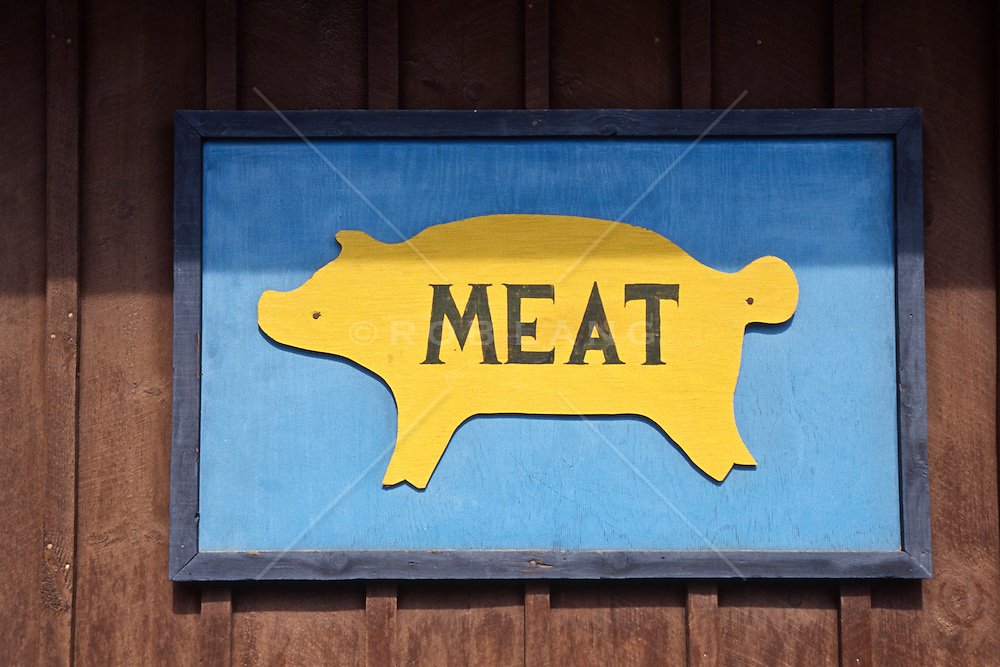 """Wooden sign with a cut out of a pig and the word """"meat"""""""