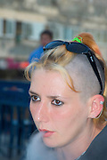 A teen aged girl with a punk hair style blowing out smoke from a cigarette